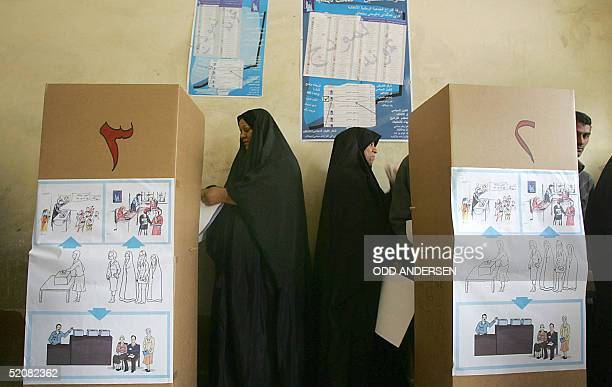 Iraqi's cram behind polling booths to vote at a school polling station in the town of Abu Al-Kahasib on the southern edge of the Iraqi city of Basra,...