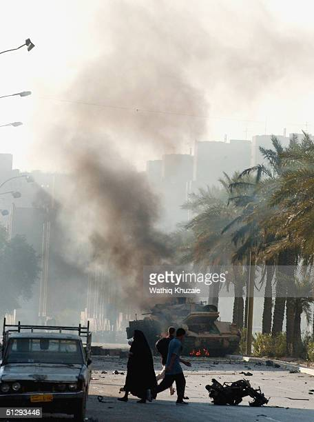 Iraqis cross the street as a US military vehicle burns in the background on September 12 2004 in Haifa Street Baghdad Iraq Fighting broke out in the...