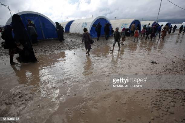 Iraqis displaced from Mosul walk around the grounds of the Hammam alAlil camp for the internally displaced south of Mosul on March 16 during an...