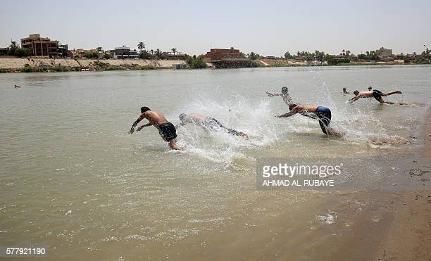 Iraqis dive into the Tigris River in the capital Baghdad on July 20 2016 on the first day of a twoday official holiday that the Iraqi authorities...