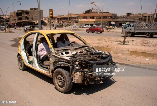 TOPSHOT Iraqis drive a car that has been stripped down in west Mosul on July 12 2017 a few days after the government's announcement of the...