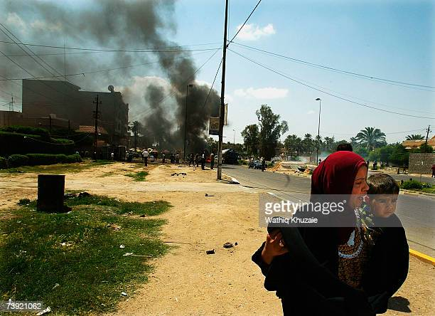 Iraqis evacuate the site of a suicide car bomb explosion in the Jadriya neighborhood on April 19 2007 in Baghdad Iraq A suicide car bomber rammed...