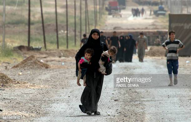 TOPSHOT Iraqis evacuate their home as Iraqi forces advance in the northwestern alHaramat neighbourhood of Mosul on May 11 during the ongoing...