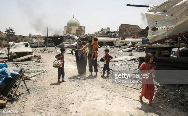 Iraqis flee from the Old City of Mosul with the destroyed AlNuri Mosque seen in the background on July 2 as Iraqi government forces continue their...