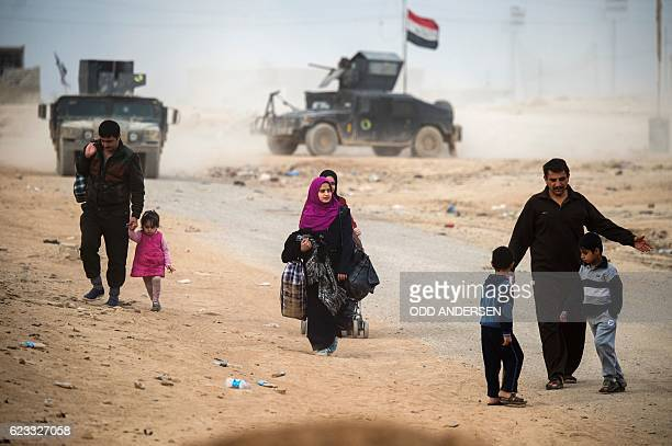 Iraqis flee to an area held by the Iraqi Special Forces 2nd division in the Samah neighbourhood of Mosul on November 15 during an ongoing operation...