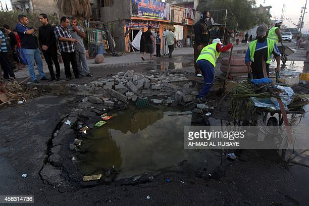 Iraqis gather around a crater left behind following a car bomb that targeted a tent set up to host Shiite pilgrims late last night leaving left six...