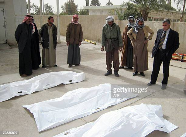 Iraqis gather around the bodies of a family killed by gunmen at a morgue in Baquba 60 kms north of Baghdad on February 19 2008 A couple and their son...