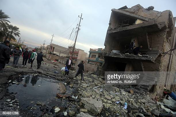 Iraqis gather at the site of a bomb attack in eastern Baghdad on January 12 2016 A bomb exploded at the cafe and a suicide bomber detonated an...