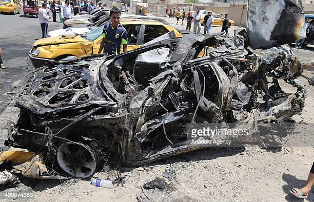 Iraqis gather at the site of a car bomb attack in the eastern AlSadr district of Baghdad Iraq on May 13 2014 At least twenty people were killed and...