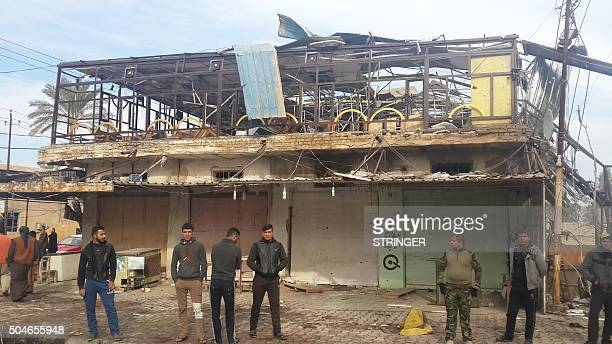 Iraqis gather at the site where a bomb exploded at a cafe and a suicide bomber detonated an explosivesrigged vehicle a day earlier in the Iraqi town...