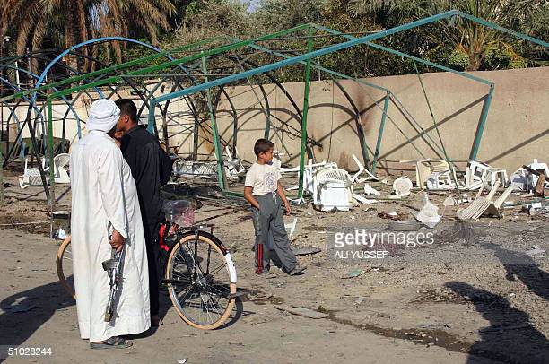 Iraqis gather in front of destroyed tents set up for the memorial service of a local official killed two days earlier before it was targeted by a...