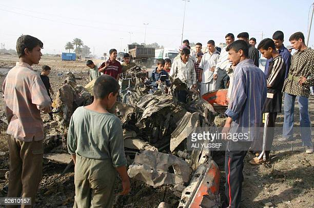 Iraqis gather looking at the debris following a car bomb early 10 April 2005 in the northeastern city of Baquba 60 kms from Baghdad The car bomb...