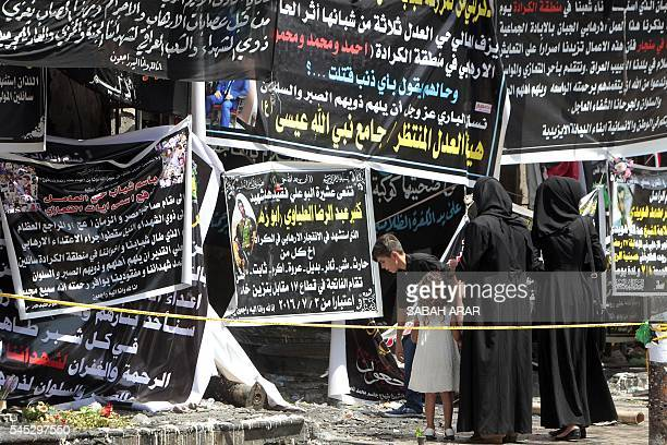 TOPSHOT Iraqis gather on July 7 2016 next to banners of condolences at a memorial for the victims of a bombing which claimed the lives of over 200...