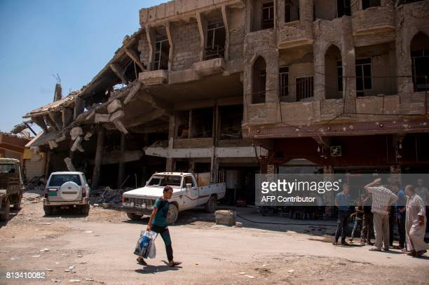 Iraqis gather outside a shop in west Mosul on July 12 2017 a few days after the government's announcement of the 'liberation' of the embattled city...