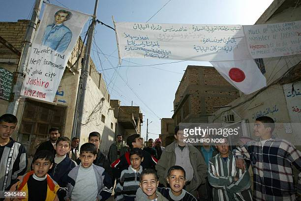 Iraqis gather under a banner welcoming Japanese troops in Samawa 270 kms south of Baghdad 08 February 2004 Japanese ground troops crossed the Kuwaiti...
