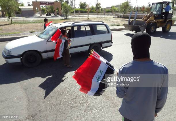 Iraqis handout their national flag in a street in the disputed norther Iraqi city of Kirkuk on October 19 2017 Iraqi government forces said they had...