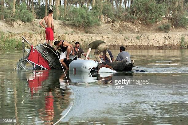 HILLAH IRAQ Iraqis help a US Marine attach a rope to a piece of wreckage of a CH46 Sea Knight helicopter that crashed May 19 2003 in the Shat...