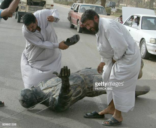 Iraqis hit a statue of Saddam Hussein with their sandals in Baghdad 09 April 2003 after it was pulled down as US tanks rolled into the heart of the...