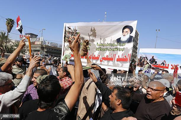 Iraqis hold banners bearing portrait of Iraq's top Shiite cleric Grand Ayatollah Ali al-Sistani during a demonstration in support of the Popular...