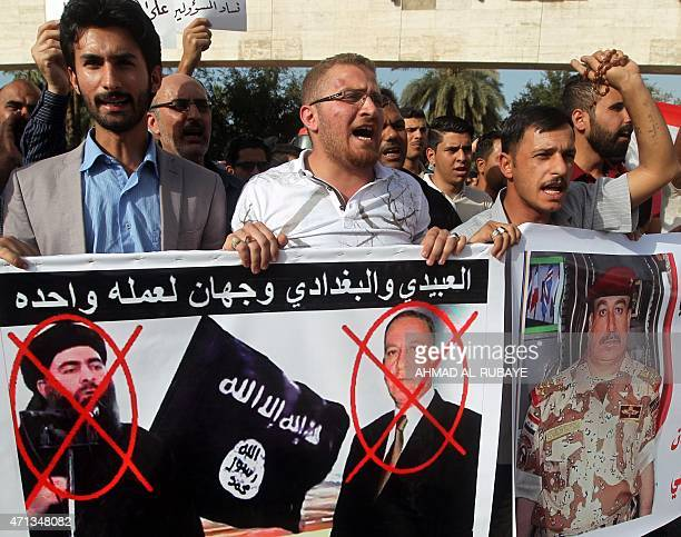 Iraqis hold banners bearing portraits of defense minister Khaled alObeidi and the leader of the Islamic State jihadist group Abu Bakr alBaghdadi...