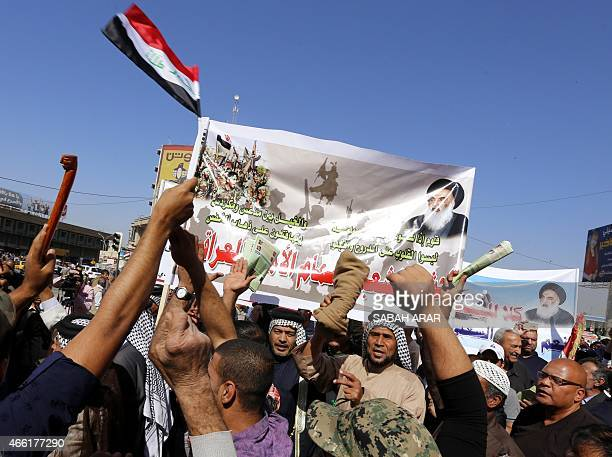 Iraqis hold banners bearing portraits of Iraq's top Shiite cleric Grand Ayatollah Ali al-Sistani during a demonstration in support of the Popular...