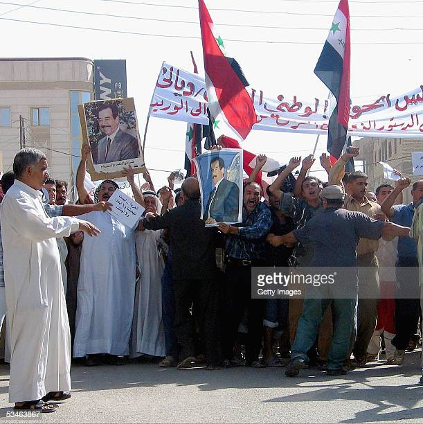 Iraqis hold pictures of ousted dictator Saddam Hussein as they take part in a demonstration against the draft of Iraq's new constitution August 26...