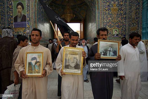 Iraqis hold portraits of religious leaders and a relative after they carry a coffin containing the remains of their relatives exhumed from a mass...