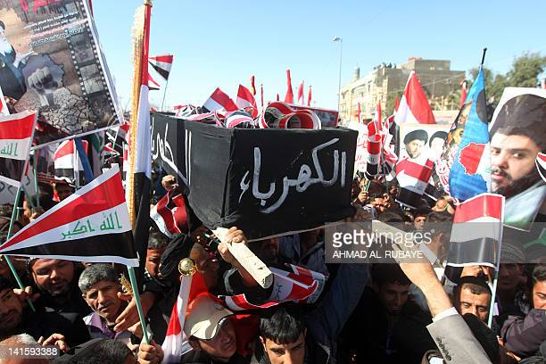 Iraqis hold up a coffin that reads in Arabic 'electricity' denoting the lack of electricity across Iraq as hundreds of thousands of supporters of the...