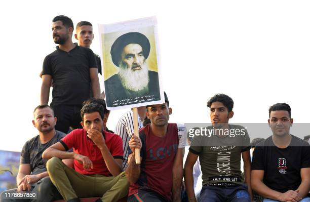 Iraqis hold up a portrait of Ayatollah Ali al-Sistani during an anti-government demonstration, on October 28, 2019 in the central city of Hila. - The...