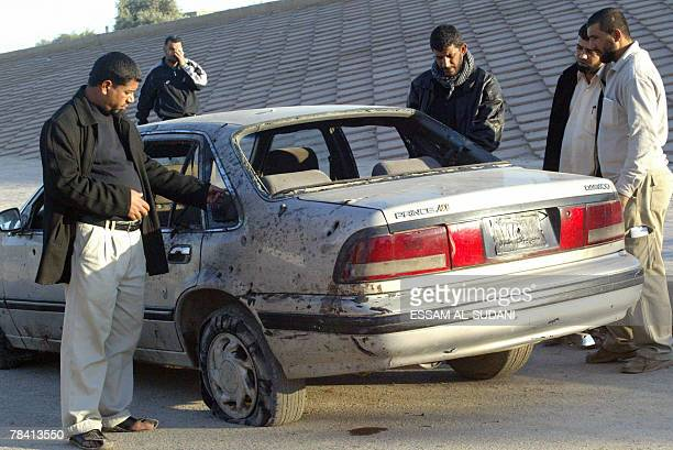 Iraqis inspect a shrapnel riddled car at the site of a car bomb in the southern Shiite city of Amara 12 December 2007 At least 28 people were killed...