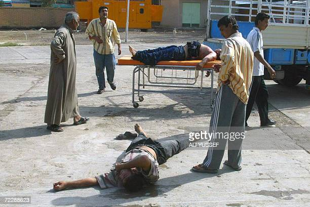 Iraqis inspect the bodies of two men killed in a local market by unknown gunmen at the local Baquba hospital morgue located 60 kms northeast of...