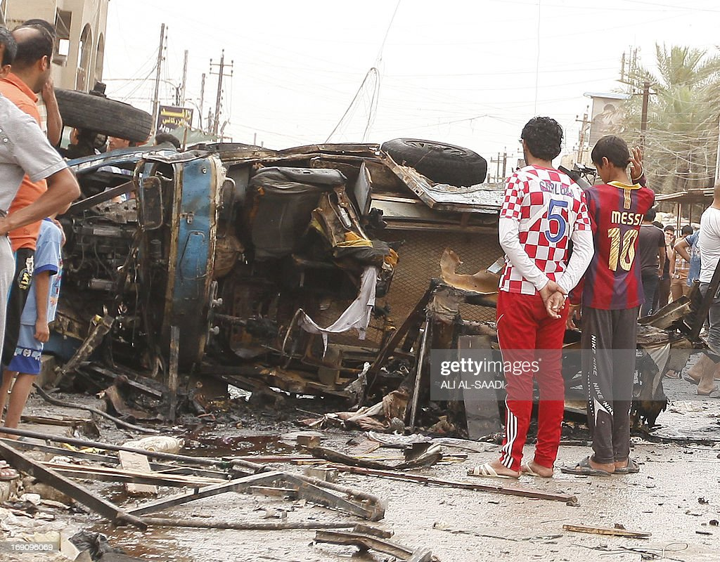 Iraqis inspect the damage following an explosion in the Kamaliya area of eastern Baghdad on May 20, 2013. A wave of 12 bomb attacks across Iraq killed at least 15 people and wounded dozens more, security and medical officials said. SAADI