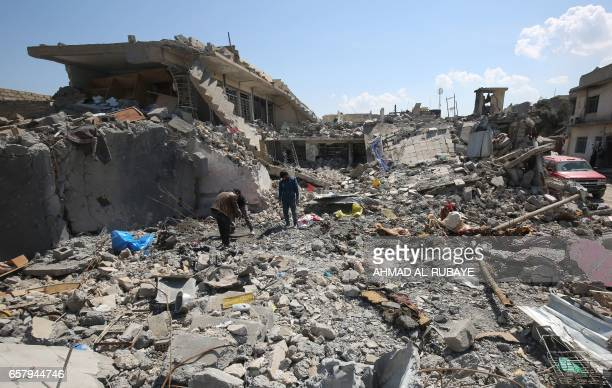 Iraqis inspect the damage in the Mosul alJadida area on March 26 following air strikes in which civilians have been reportedly killed during an...