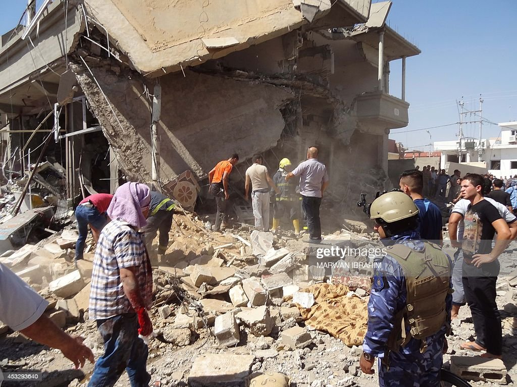 Iraqis inspect the scene of a car bomb explosion outside the Shiite Mustafa prayer hall, or Husseiniya, in the southwest of the northern Kurdish controlled Iraqi city of Kirkuk on August 7, 2014. A series of blasts outside Shiite prayer halls killed four people and wounded 19 others police and medical sources said.