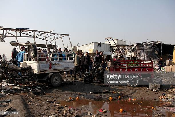 Iraqis inspect the scene of car bomb attack at a market in Baghdad Iraq on January 8 2017 At least ten civilians were killed and 18 others injured...