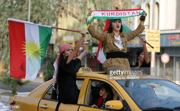 Iraqis Kurdish women celebrate with the Kurdish flag as they ride outside the windows and roof of a taxi in the northern city of Kirkuk on September...