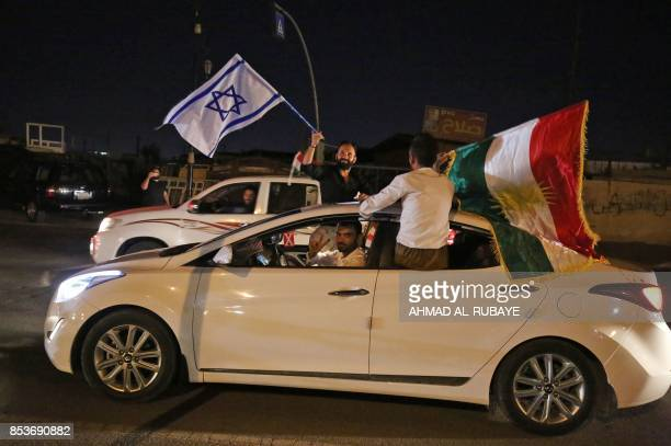 Iraqis Kurds carry the Kurdish and the Israeli flags in the streets of the northern city of Kirkuk on September 25 2017 following a referendum on the...