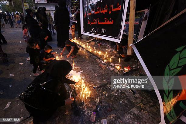 Iraqis light candles on July 10 2016 at the site of a suicidebombing attack which took place on July 3 in Baghdad's Karrada neighbourhood The Baghdad...