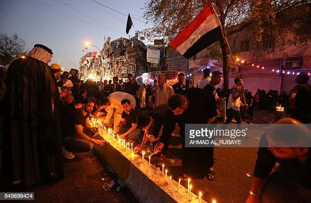 TOPSHOT Iraqis light candles on July 9 2016 at the site of a suicidebombing attack which took place on July 3 in Baghdad's Karrada neighbourhood The...