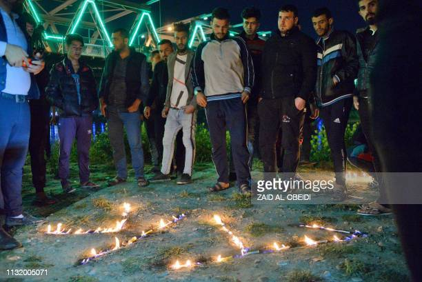 Iraqis light up candles in remembrance for the victims of the capsized ferry in the northern Iraqi city of Mosul on March 22 a day following the...