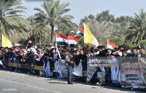 Iraqis line up the road leading to Baghdad International Airport as they welcome the pontiff upon his arrival on March 5 at the start of the first...