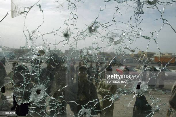 Iraqis look at a bulletriddled shop window in Baghdad's suburb of Abu Gharib 01 November 2003Medical sources and witnesses said at least four Iraqis...