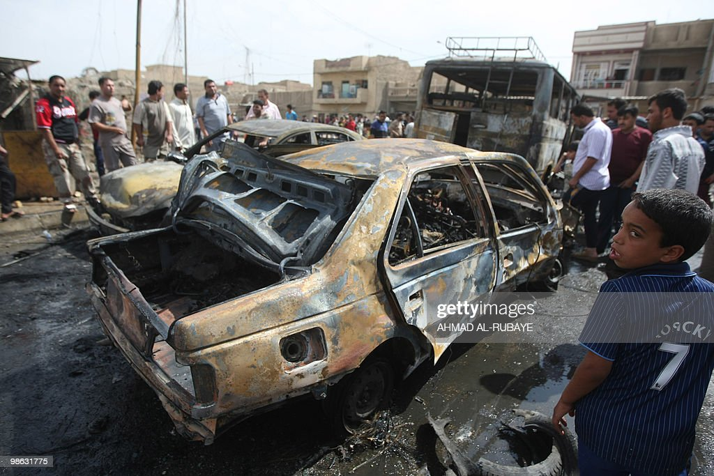 Iraqis look at a car destroyed when a car bomb exploded on April 23, 2010 in the impoverished Baghdad district of Sadr City. A series of five car bombs, three during prayers at Shiite mosques in Baghdad, and other attacks across Iraq killed 58 people, days after the government said Al-Qaeda was on the run.