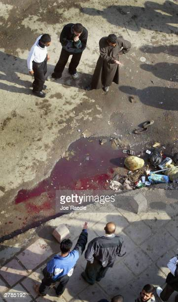 Iraqis look at blood spilled on the spot where a homemade bomb killed at least four Iraqis and one American soldier when it exploded as a US army...