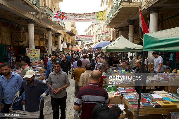 Iraqis look at books displayed outside bookshops on alMutanabi street in central Baghdad on October 29 2016 The famous street which was inaugurated...