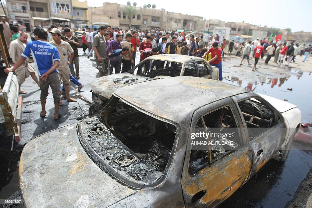 Iraqis look at burned cars at the scene of a car bomb explosion on April 23, 2010 in the impoverished Baghdad district of Sadr City. A series of five car bombs, three during prayers at Shiite mosques in Baghdad, and other attacks across Iraq killed 58 people, days after the government said Al-Qaeda was on the run.