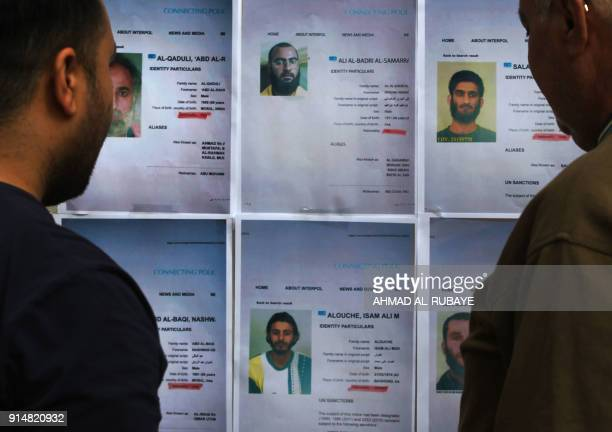 Iraqis look at printed profiles of Islamic State group members released by Iraqi authorities on February 6 2018 Iraqi authorities issued a new list...