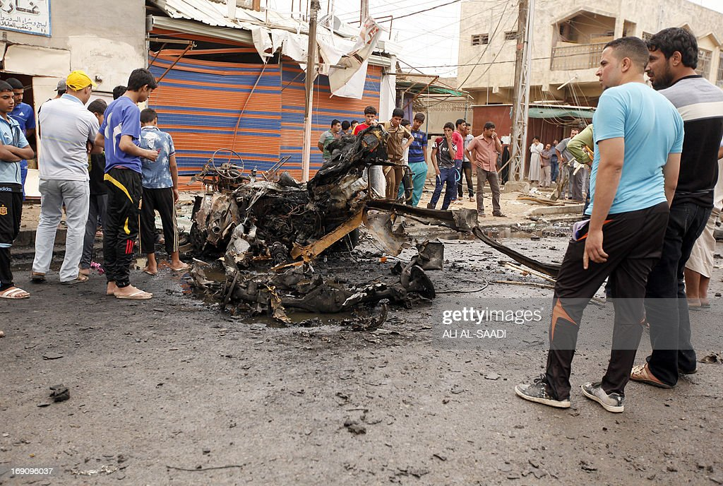 Iraqis look at the remains of a car bomb that detonated in the Kamaliya area of eastern Baghdad on May 20, 2013. A wave of 12 bomb attacks across Iraq killed at least 15 people and wounded dozens more, security and medical officials said. SAADI