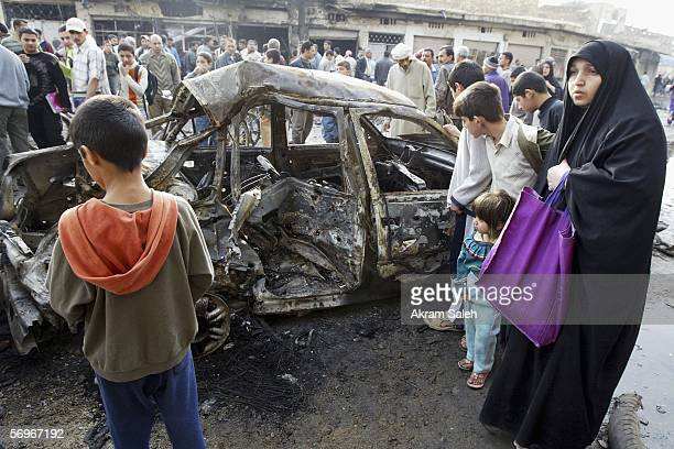 Iraqis look on at the site of a car bomb explosion in the alHurriya neighborhood on March 1 2006 in Baghdad Iraq A car bomb exploded on the evening...