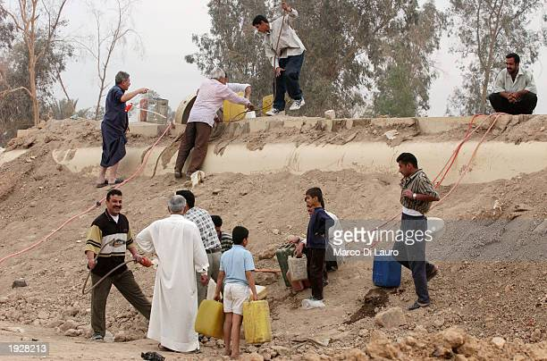 Iraqis loot gasoline from tanks which have been buried underground by theIraqi regime April 13 2003 in Baghdad Iraq Widespread looting continues all...